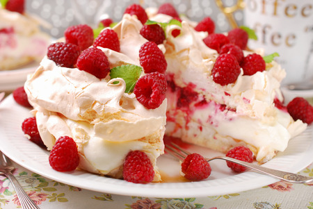 meringue  pavlova cake with whipped cream,caramel and fresh raspberries Archivio Fotografico