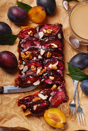 homemade style: piece of homemade plum cake with almond flakes and walnuts on old paper-top view Stock Photo