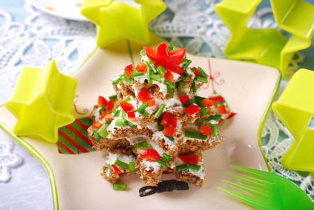 person appetizer: christmas tree made from stack of star shape dark bread with cheese,chive and red pepper for breakfast
