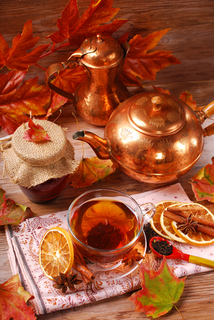 glass of autumn tea with orange ,spices and honey on wooden table photo