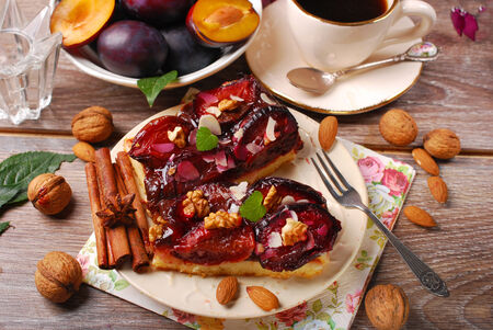 piece of homemade plum cake with nuts and spices,fresh fruits  and cup of coffee photo