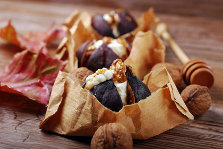 baked figs with goat cheese,walnuts and honey in paper baskets on wooden table photo