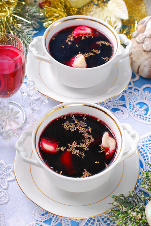 supper: traditional red borscht in cups and dumplings stuffed with mushrooms for christmas eve supper Stock Photo