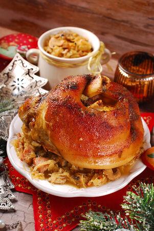 roasted pork knuckle served with bigos (sauerkraut ) for christmas dinner photo
