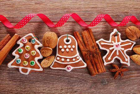 christmas wooden background with homemade gingerbread cookies ,spices and red ribbon photo