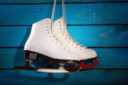 figure skating: pair of white ice skates for girl hanging on blue wooden background