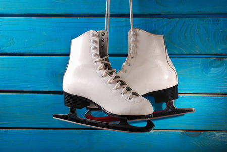 pair of white ice skates for girl hanging on blue wooden background