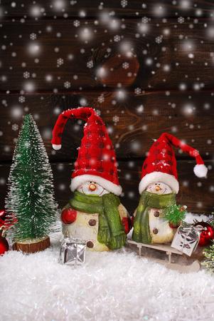 weihnachtsmann lustig: Weihnachtsdekoration mit zwei lustigen Weihnachtsmann-Figuren auf Holzuntergrund