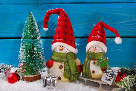 weihnachtsmann lustig: Weihnachtsdekoration mit zwei lustigen Weihnachtsmann-Figuren auf blauem Holzuntergrund