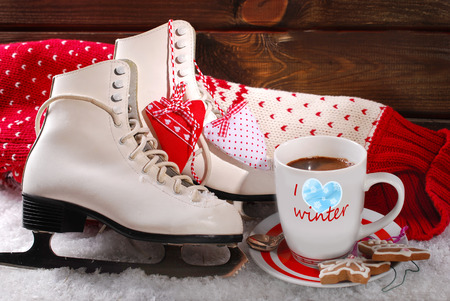 ice skates: cup of coffee,pair of white ice skates ond wool sweater on snow