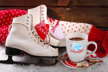 patinaje sobre hielo: taza de café, un par de patines de hielo blancos ond suéter de lana en la nieve Foto de archivo