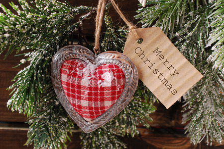christmas  card with vintage heart and paper gift tag for greetings hanging on fir branch photo