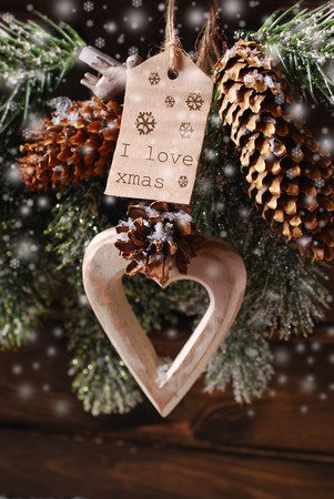 wooden heart and paper tag for christmas greetings hanging on fir branch with cones photo