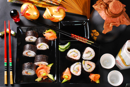 sushi set with salmon,avocado and cucumber on black plates photo