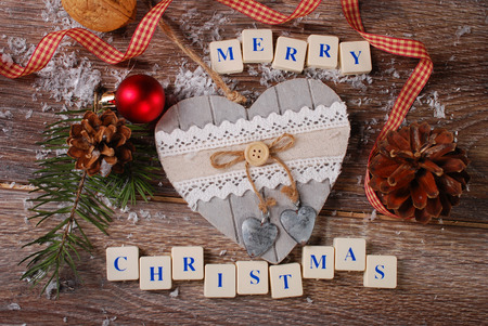 christmas card with greetings made of  letter cubes with vintage heart on wooden background photo