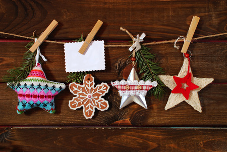 collection of various christmas stars with greeting card hanging on twine against wooden background photo