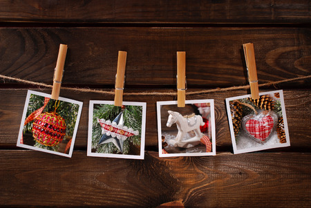 four vintage style christmas  photos hanging on rope with bamboo clothespins against old wooden background photo