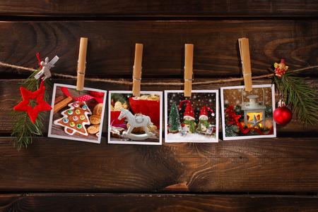 vier kerst foto's opknoping op touw met bamboe wasknijpers tegen oude houten achtergrond Stockfoto
