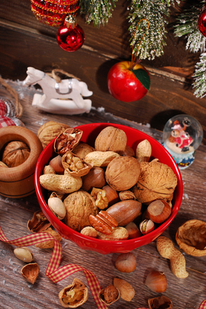 nuts assortment in red bowl and nutcracker on wooden table for christmas-top view photo
