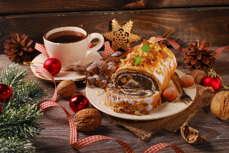 poppy seed cake with nuts and dried fruits and cup of coffee for christmas on rustic wooden table