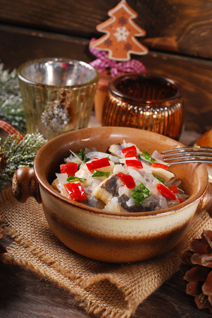 homemade style: herring salad with onion,red pepper and oil for christmas served in rustic style on wooden table