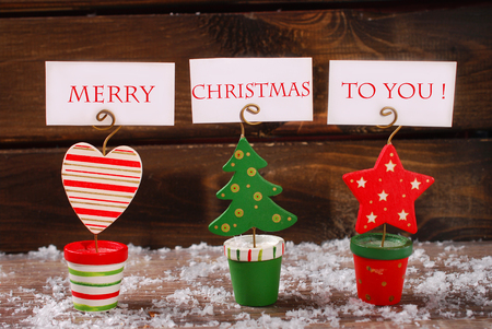 three wishes: three christmas greeting card holders in christmas tree ,star and heart shapes with wishes on wooden table