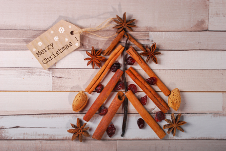 tree nuts: christmas tree made of spices and nuts on old wooden background
