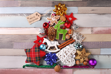 christmas tree made of various colorful decorations on old wooden background photo