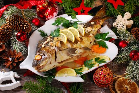 geroosterde hele karper gevuld met groenten en amandelen op houten tafel voor kerst Stockfoto