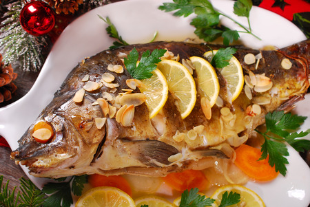 roasted whole carp stuffed with vegetables and almonds on wooden table for christmas