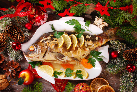 roasted whole carp stuffed with vegetables and almonds on wooden table for christmas-top view