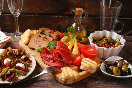 mediterranean appetizers and antipasti with olives,mozzarella,dried tomatoes on wooden table photo