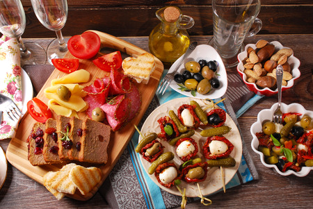 antipasti: mediterranean appetizers and antipasti with olives,mozzarella,dried tomatoes on wooden table