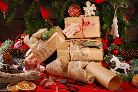 christmas wrapping: wrapping christmas presents  in eco paper with homemade decoration on wooden background