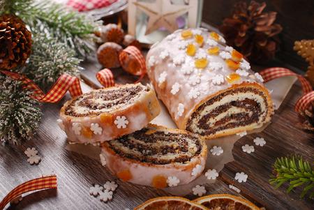 weihnachtskuchen: Weihnachtsmohnkuchen mit Zuckerguss glasiert, Orangenschale und Schneeflocken besprüht auf Holztisch