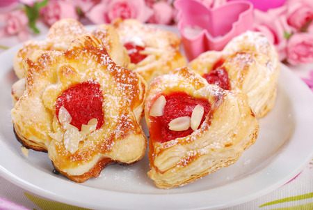 heart and flower shaped puff pastry cookies with strawberries on white plate for valentines photo