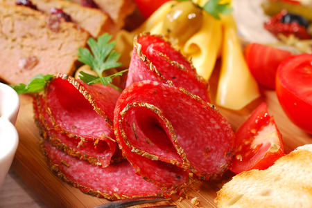 salami slices: salami slices,pate,cheese and vegetables on wooden board