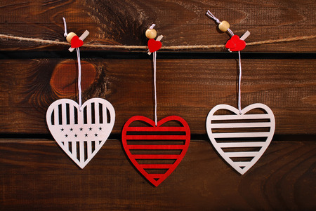 darkroom: valentine red and white hearts hanging on twine against wooden background