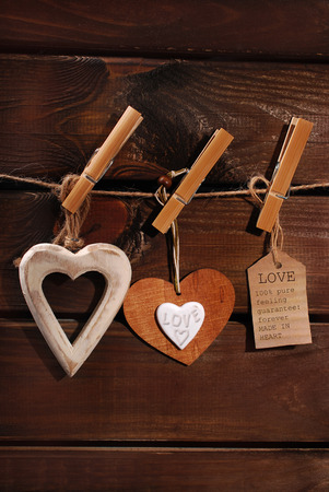 darkroom: valentine hearts and paper tag hanging on twine against wooden background
