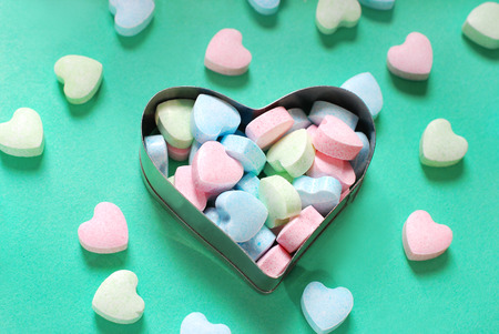 cookie cutter: pastel powder sugar candies in heart shaped cookie cutter on green background