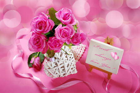 bunch of roses and little easel with love declaration text on pink background photo