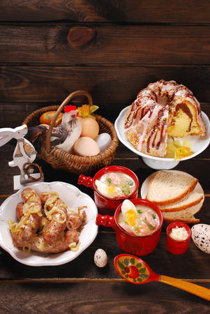 easter white borscht,sausage , ring cake with icing and chocolate glaze on rural wooden background photo