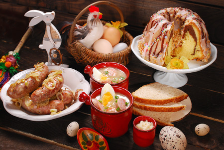 polish chicken: easter white borscht,sausage , ring cake with icing and chocolate glaze on rural wooden background Stock Photo