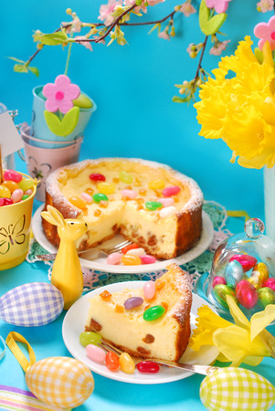 homemade cheesecake with raisins and egg shaped candies decoration on easter table photo
