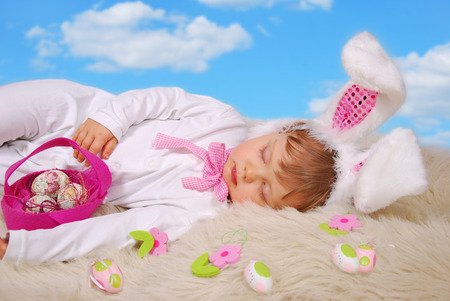 beautiful sleeping baby girl in easter bunny costume with eggs in pink felt basket