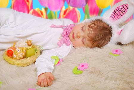 beautiful sleeping baby girl in easter bunny costume with eggs in basket