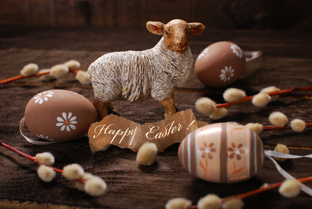 easter rustic decoration with sheep figurine and eggs on wooden background photo
