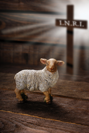 offered: easter concept with cross in light rays and lamb as a symbol of  sacrifice offered to God Stock Photo