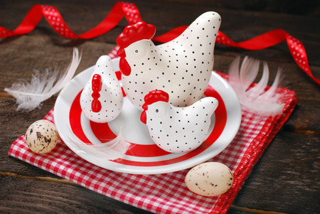 easter decoration with three white - red clay hens  on plate photo
