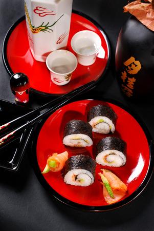 japanese sake: rollos de sushi maki japoneses establecidos con salmón y aguacate en la placa roja y el sake Foto de archivo